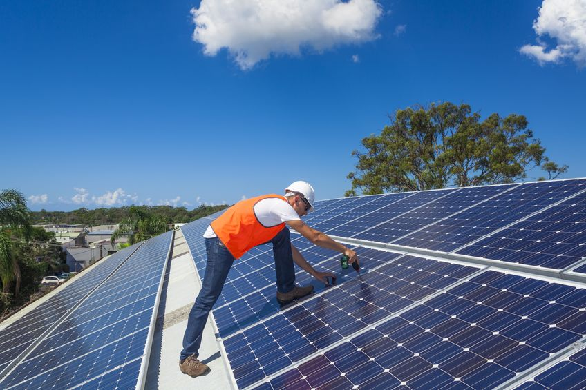 21361833 – young technician installing solar panels on factory roof
